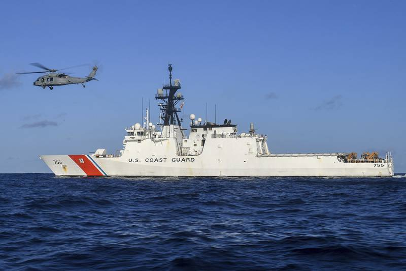 In this Aug. 25, 2020, photo provided by the U.S. Navy, an MH-60S Sea Hawk helicopter hovers next to the Legend-class cutter USCGC Munro in the Pacific Ocean.