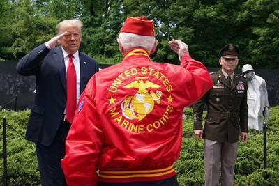 President Donald Trump salutes a veteran during a visit to the Korean War Veterans Memorial in Washington on June 25, 2020.