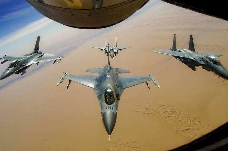 Two U.S. Air Force F-16 Fighting Falcons fly in formation with two Royal Saudi Air Force F-15E Strike Eagles after receiving fuel from a KC-135R Stratotanker during a routine exercise over Southwest Asia, Dec. 15, 2020.